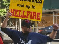 "A protestor holds a sign that reads ""Homosexuals end up in Hellfire."""